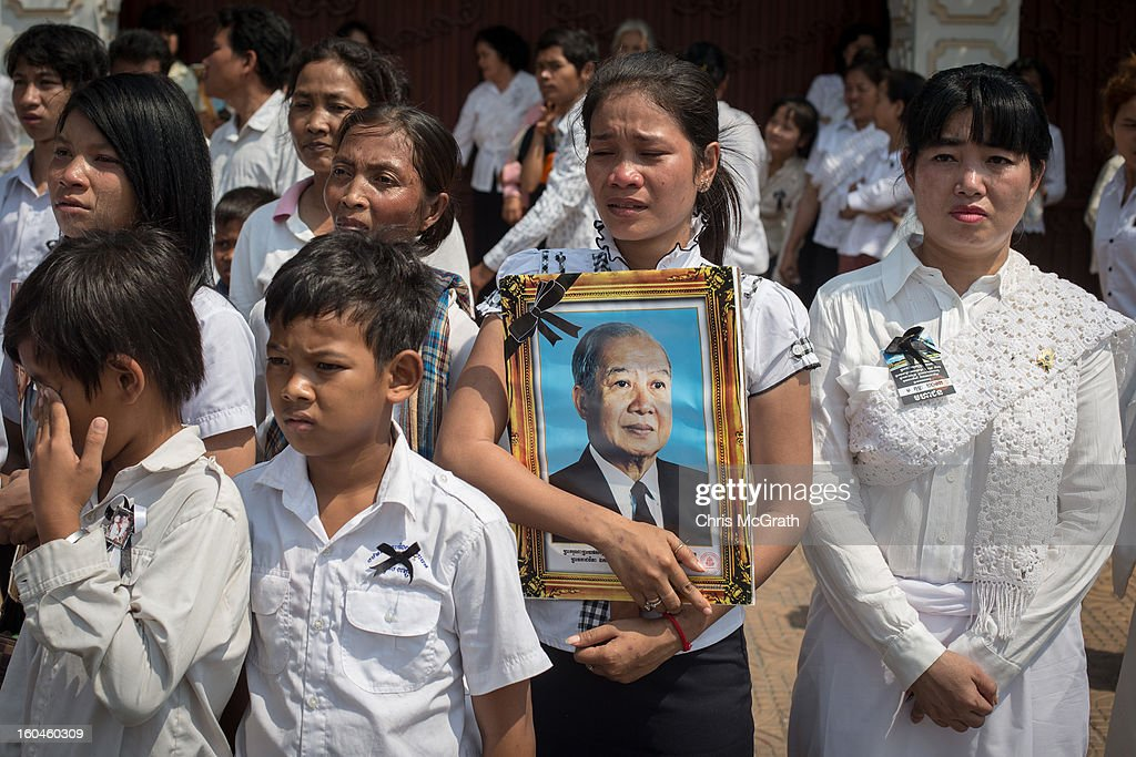 People gather outside the crematorium to catch a glimpse of the coffin carrying the body of former King Norodom Sihanouk on February 1, 2013 in Phnom Penh, Cambodia. Over half a million mourners lined the streets to pay their respects during the funeral procession which finished at the crematorium where his funeral pyre will be lit by his wife and son on the 4th of February. King Norodom Sihanouk died of a heart attack last October in Beijing at the age of 89. For the past three months his body has been lying in state at the Royal Palace.