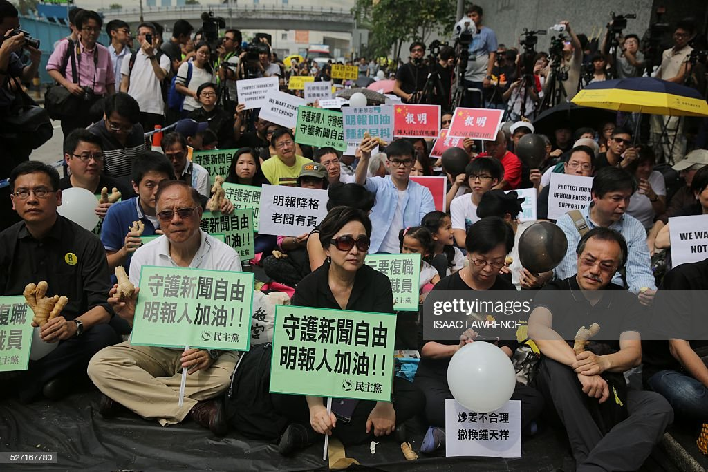 People gather outside the offices of Ming Pao during a rally organised by Journalist groups to protest the sacking of Ming Pao's Executive Chief Editor Keung Kwok-yuen in Hong Kong on May 2, 2016. / AFP / ISAAC