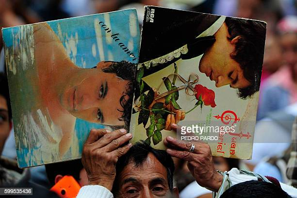 People gather outside the Palace of Fine Arts to pay tribute to Mexico's late Latin music legend Juan Gabriel in Mexico City on September 5 2016 The...