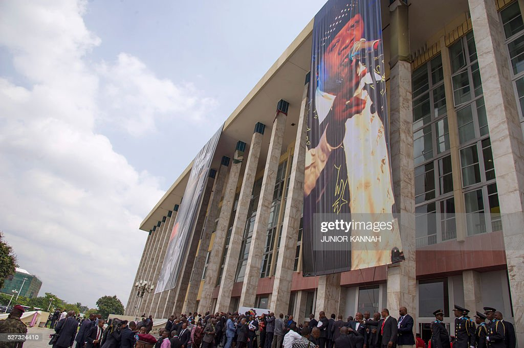People gather outside the Palais du Peuple in Kinshasa to pay tribute to late rumba musician Papa Wemba on May 2, 2016. Democratic Republic of Congo's rumba king Papa Wemba was posthumously awarded one of his country's highest honours, a week after he collapsed on stage and died aged 66. / AFP / JUNIOR