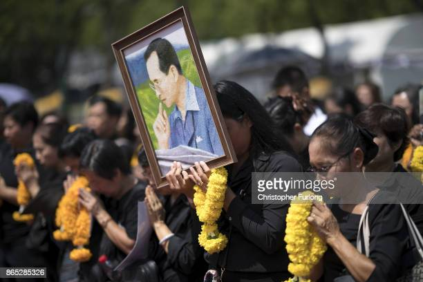 People gather outside the Royal Palace to pay their respects to Thailand's late King Bhumibol Adulyadej as the city prepares for his cremation on...