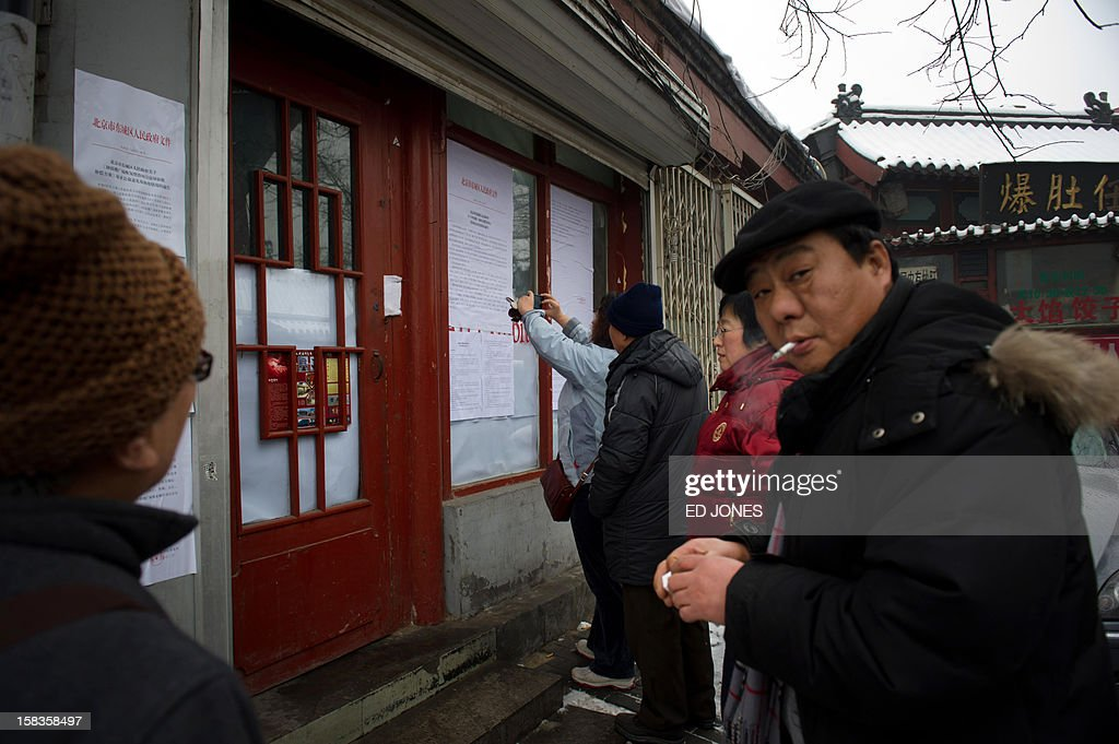 People gather round a demolition notice in a 'hutong' area near the 13th century historic Drum and Bell Tower in Beijing on December 14, 2012. China's capital is to destroy swathes of ancient courtyard homes around a 13th-century landmark in what is being called an effort to preserve Beijing's historical legacy, residents said. Large numbers of hutong homes, some of them dating back to the Qing dynasty, will be demolished around the Drum and Bell Tower -- a tourist hotspot in Beijing's historic centre -- to make way for a large plaza, they said. AFP PHOTO / Ed Jones