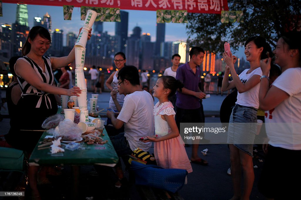 People gather the beer cups as they drink beer in the night on August 4, 2013 in Chongqing, China. Chongqing is a major city in southwest China and became the municipality was created on 14 March 1997. It known as a 'Mountain City' and 'River City' was constructed on the mountain and along the Yangtze River.