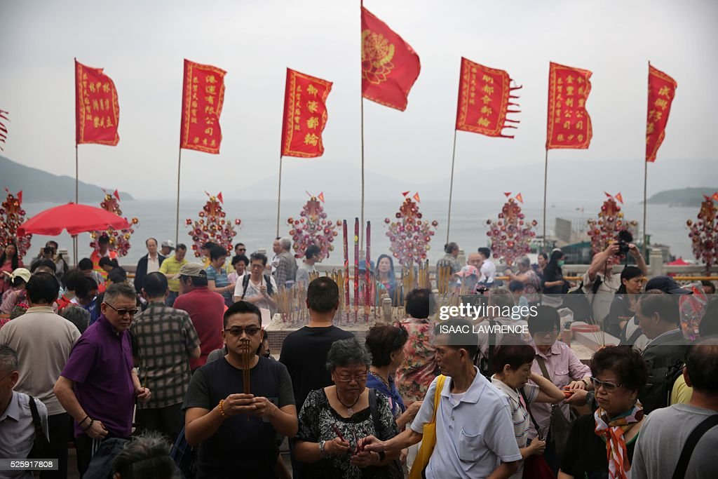 People gather to burn joss sticks outside the Joss House Bay Tin Hau temple during celebrations for the Tin Hau Festival in Hong Kong on April 29, 2016. Tin Hau is the Goddess of the Sea and patron saint of fishermen - On her birthday, locals flock to the more than 70 temples dedicated to her to pray for safety, security, fine weather and full fishing nets during the coming year. / AFP / ISAAC