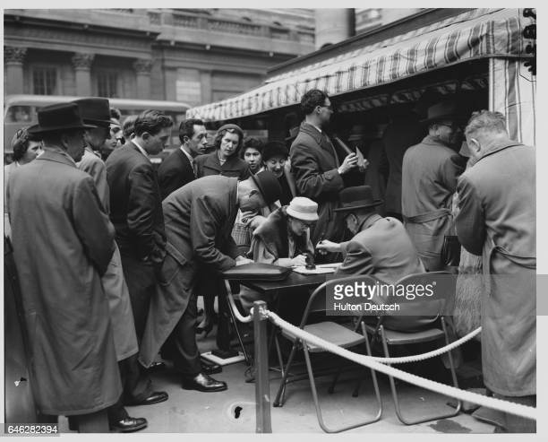 People gather to buy premium savings bonds in front of the Royal Exchange on the first day they are offered for sale