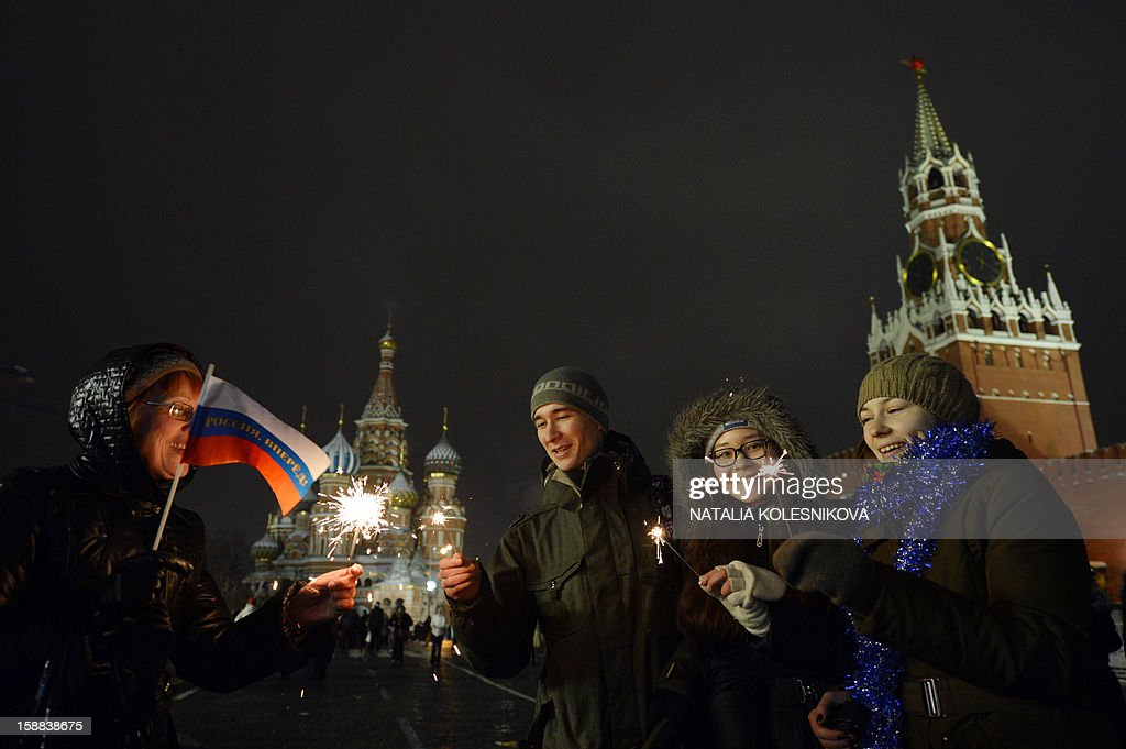People gather to celebrate the New Year at the Red Square in front of St.Basil cathedral in Moscow, early on January 1, 2013. Tens of thousands of people gathered on the Red Square to celebrate the New Year at midnight.