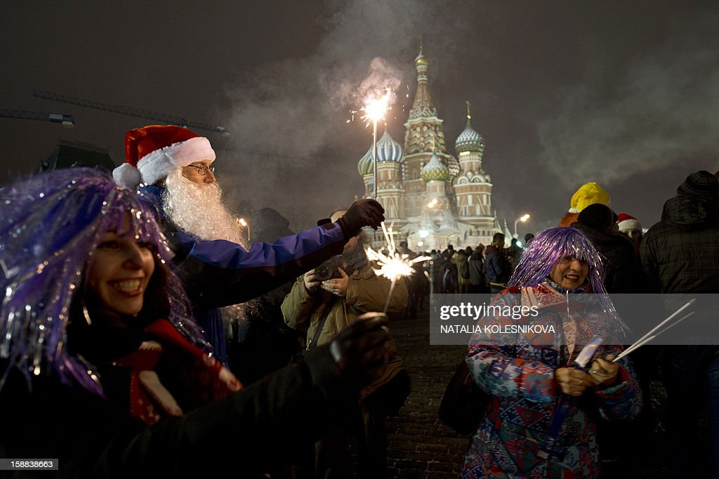 People gather to celebrate the New Year in front of St.Basil cathedral at the Red Square in Moscow, early on January 1, 2013. Tens of thousands of people gathered on the Red Square to celebrate the New Year at midnight.