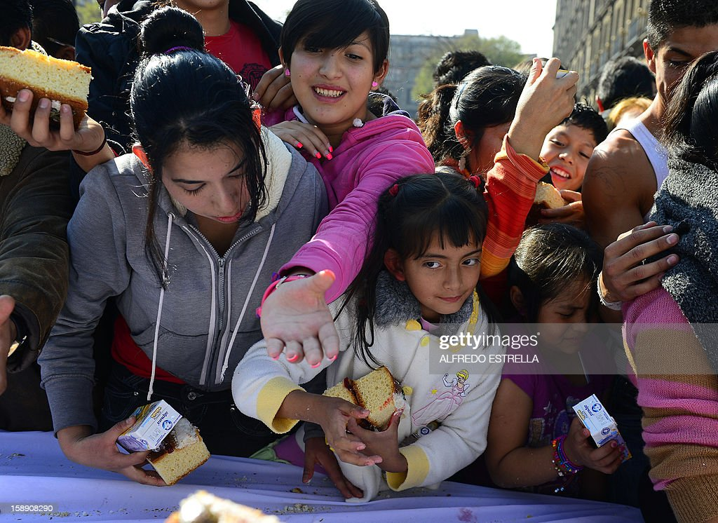 People gather to get a piece of the traditional 'Rosca de Reyes' (Mexican Epiphany Bread) --a large ring-shaped bread roll baked for Epiphany-- in Mexico City, on January 3, 2012. The 1900-metre circumference 'Rosca de Reyes', weighing 10 metric tons --the world biggest-- was distributed among 200,000 people at Zocalo Square in the Mexican capital. AFP PHOTO/Alfredo ESTRELLA