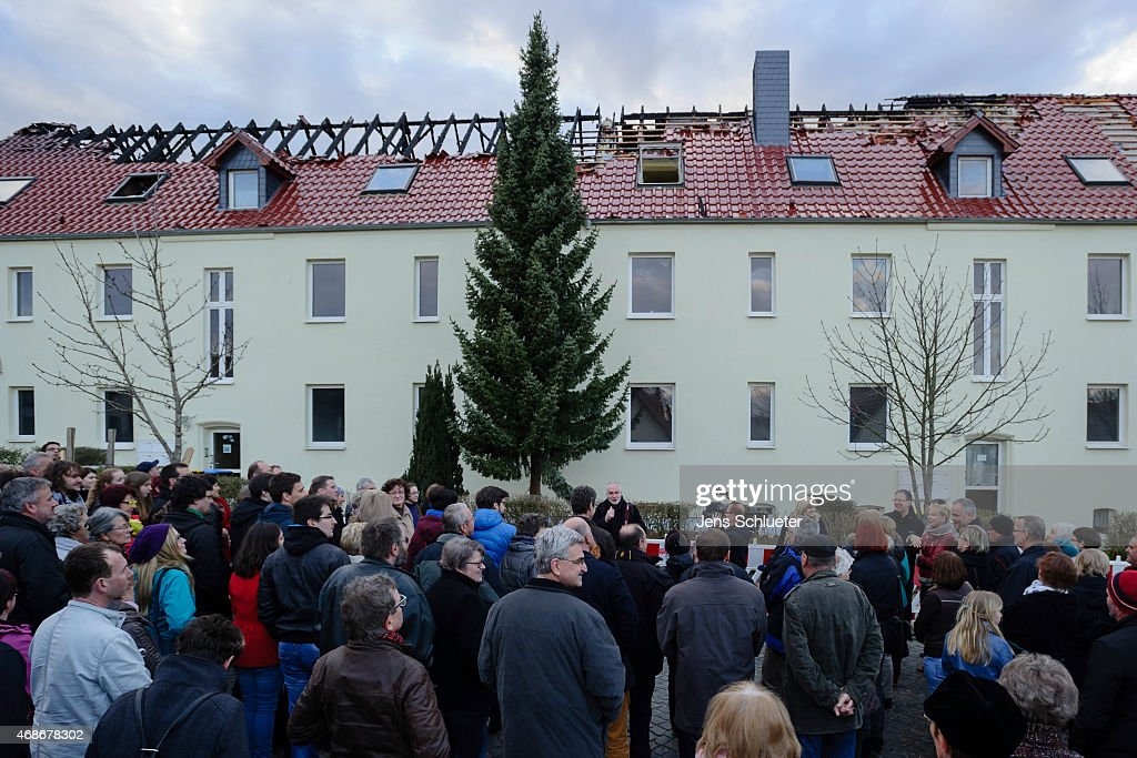 People gather to hold an evening vigil for peace to demonstrate against the recent arson attack against a facility for housing refugees on April 5...