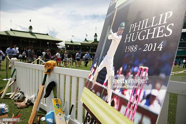 People gather to lay flowers and messages at the Randwick End of the SCG following the gathering of people to watch the funeral service held in...