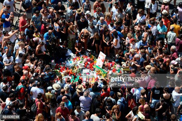 TOPSHOT People gather to leave candles flowers messages stuffed toys and many differents objects for the victims on August 18 2017 at the spot where...