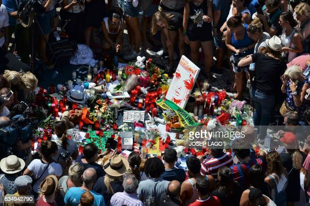 People gather to leave candles flowers messages stuffed toys and many differents objects for the victims on August 18 2017 at the spot where...