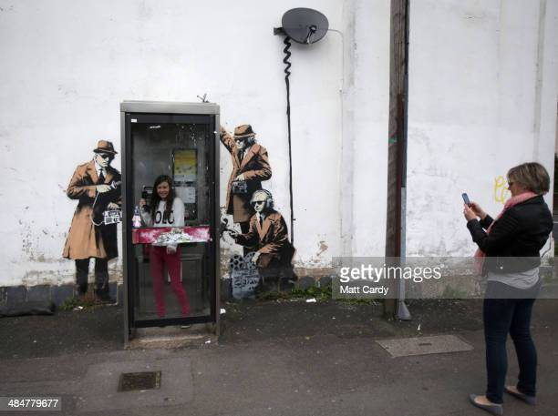 People gather to look and photograph a piece of new graffiti street art claimed to be by the secretive underground guerilla artist Banksy which...