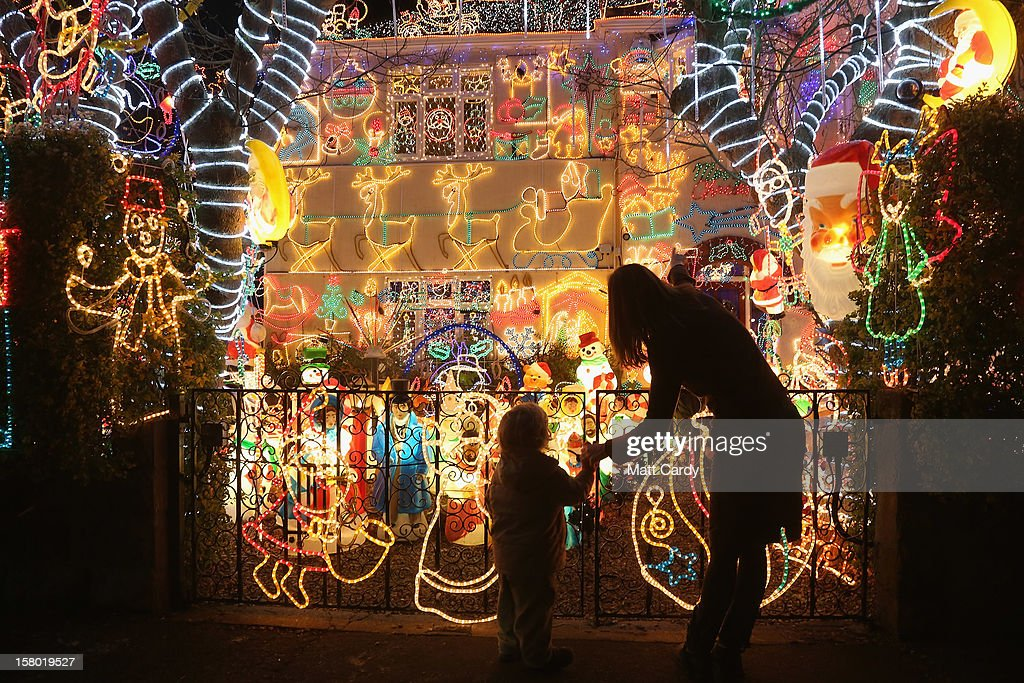 People gather to look at Christmas festive lights that adorn a detached house in a suburban street in Melksham, December 8, 2012 in Melksham, England. The lights, a popular festive attraction, have returned to the town after a two-year absence and have raised thousands of pounds for charity for a local hospice, Dorothy House. The display, which is estimated to involve over 100,000 bulbs, worth over 30,000 GBP and even needed an up-rated electricity supply installed to cope with the additional power needed, is the brainchild of householder and electrician Alex Goodhind. This year, the display which Mr Goodhind began fifteen years ago now takes a team of professional electricians five weeks to complete, and even includes a snow machine.