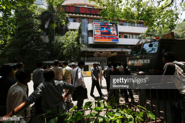 People gather to look up at an electronic screen showing television coverage of the Indian general election at the Bombay Stock Exchange in Mumbai...