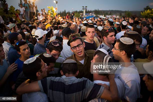 People gather to mourn during the funeral ceremony held for the three Israeli teenagers found dead on July 1 2014 in Modiin Israel The bodies of Eyal...