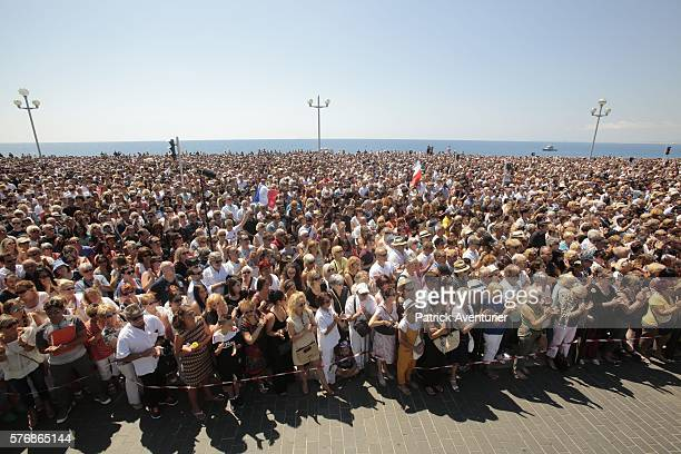 People gather to observe a minute's silence in tribute to the victims of the deadly Nice attack at La Promenade des Anglais on July 18 2016 in Nice...