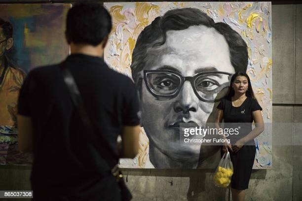 People gather to pay their respects next to a painting of Thailand's late King Bhumibol Adulyadej as the city prepares for his cremation on October...