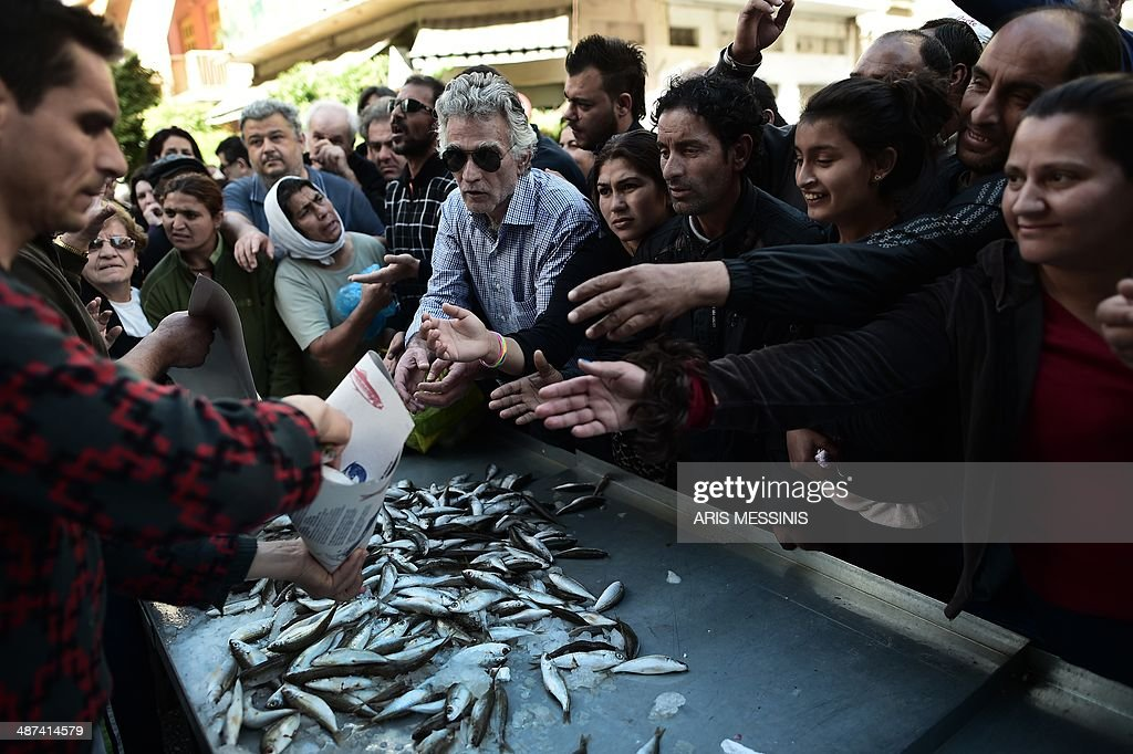 People gather to receive free fish distributed by Greek fruit and vegetable producers of open-air markets and vendors in Athens on April 30, 2014. Unions of farmers and open-air market vendors have launched an indefinite strike to oppose the sweeping liberalisation drive of their sector demanded by international bailout rescue creditors. Greece is returning to growth after six years in a recession which has shrank the economy by a quarter, but it is still saddled with a debt mountain equal to 175 percent of GDP, according to Eurostat.