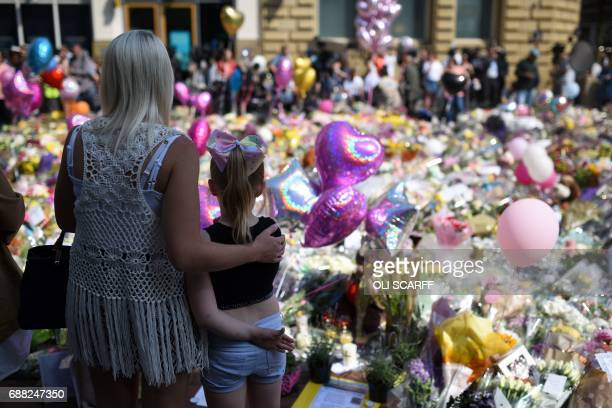 TOPSHOT People gather to see flowers and messages of support in St Ann's Square in Manchester northwest England on May 25 placed in tribute to the...