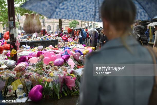 People gather to see flowers and messages of support in St Ann's Square in Manchester northwest England on May 30 placed in tribute to the victims of...