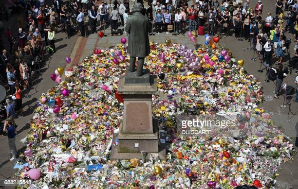 TOPSHOT People gather to see flowers and messages of support left around a statue of Richard Cobden is St Ann's Square in Manchester northwest...