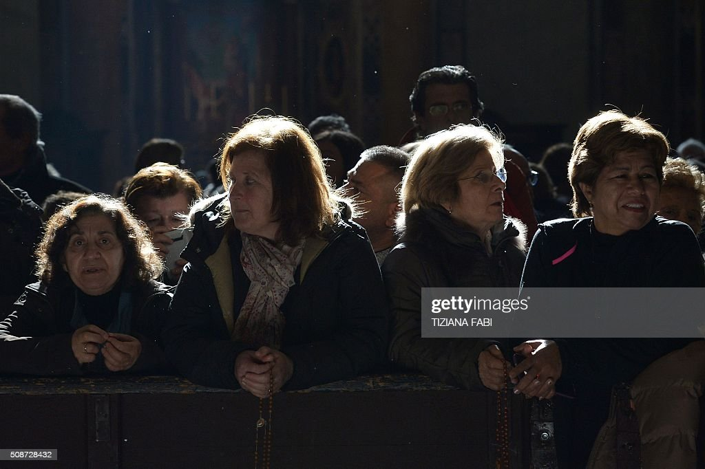 People gather to see the embalmed corpses of St Padre Pio and St Leopold Mandic displayed in St Peter's basilica, on February 6, 2016 in Vatican. Pio was revered during his lifetime (1887-1968) and his popularity has continued to grow since his death, particularly in Italy, where mini-statues and pictures of the mystical Capuchin friar are ubiquitous. / AFP / TIZIANA FABI
