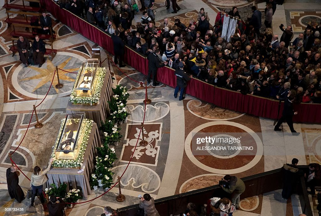 People gather to see the embalmed corpses of St Padre Pio and St Leopold Mandic displayed in St Peter's basilica, on February 6, 2016 in Vatican. Pio was revered during his lifetime (1887-1968) and his popularity has continued to grow since his death, particularly in Italy, where mini-statues and pictures of the mystical Capuchin friar are ubiquitous. / AFP / POOL / Alessandra Tarantino