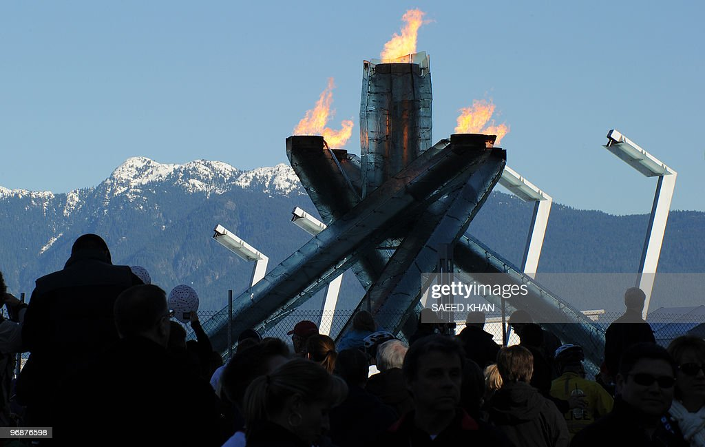 People gather to see the Olympic torch outside the Main Press Center on the seventh day of the Winter Olympics in Vancouver on February 19 2009 The...
