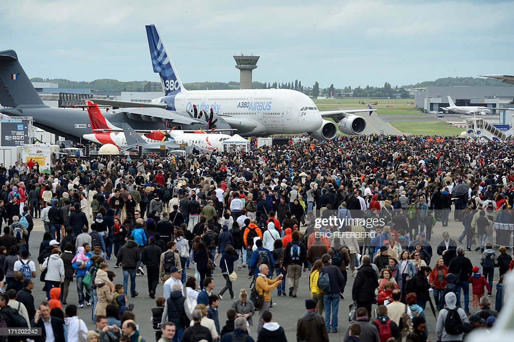 People gather to view planes, including an Airbus A 380 (C), an Airbus A400M (L) and a twin-engine ATR regional airliner (front) at Le Bourget airport, near Paris on June 23, 2013 on the last day of the 50th International Paris Air show. AFP PHOTO / ERIC FEFERBERG