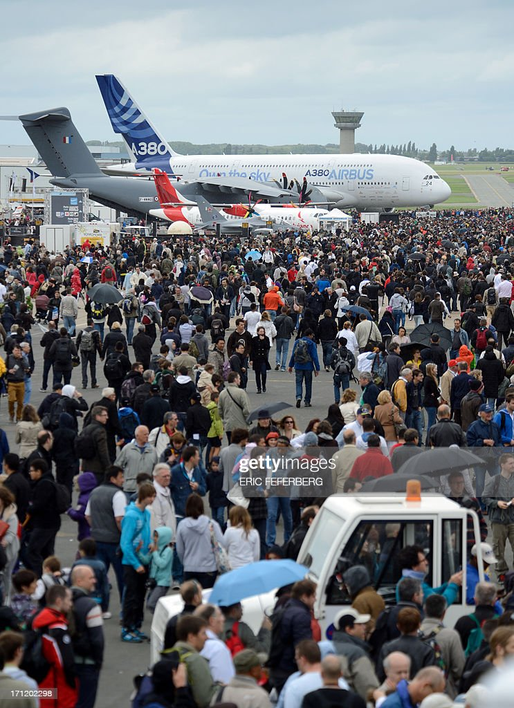 People gather to view planes, including an Airbus A 380 and a twin-engine ATR regional airliner, at Le Bourget airport, near Paris on June 23, 2013 on the last day of the 50th International Paris Air show.