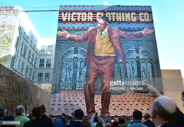 People gather to view the restoration by muralist eloy for Anthony quinn mural