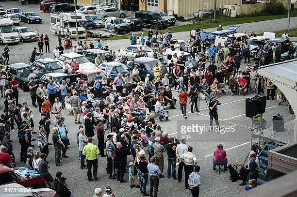 People gather to watch as asylum seekers' abandoned cars are auctioned in Salla northern Finland on July 15 2016 Over 100 old Russianmade cars driven...