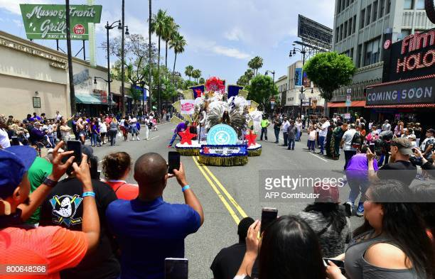 People gather to watch as Carnival dancers in a float leading the parade make their way along Hollywood Boulevard at the 6th annual Hollywood...