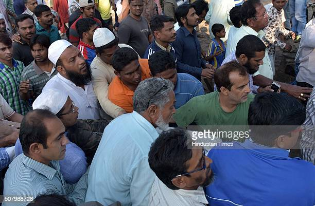 People gather to watch as the body of the 14th and the last student is recovered by rescue team at MurudJanjira beach at the Arabian Sea coast on...
