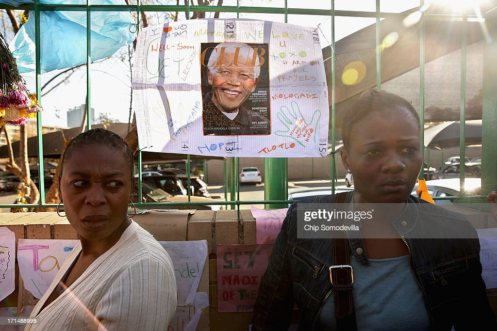 People gather to watch television news reporters outside of the Mediclinic Heart Hospital where former South African President Nelson Mandela is being treated June 25, 2013 in Pretoria, South Africa. South African President Jacob Zuma confirmed on June 23 that Mandela's condition has become critical since he was admitted to the hospital over two weeks ago for a recurring lung infection.