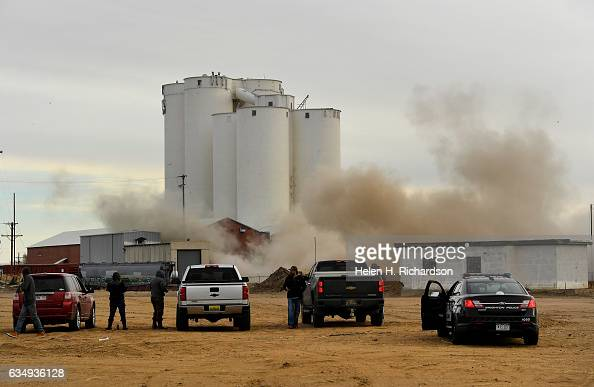 People gather to watch the 100 year old Great Western Sugar Factory smokestack fall to the ground as it is demolished on the old factory site on...