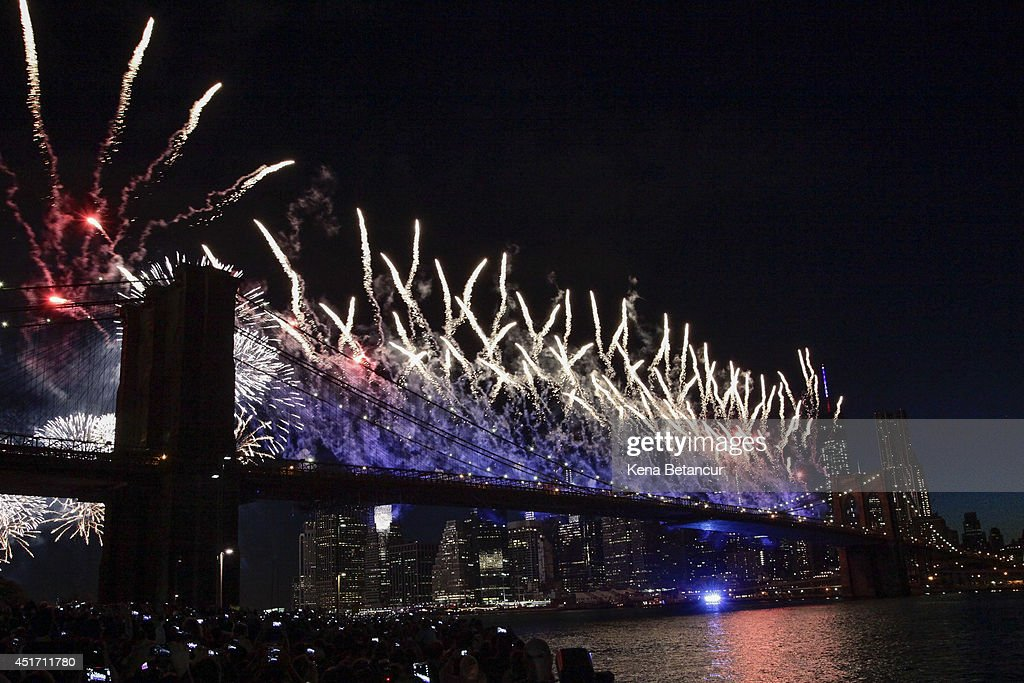 People gather to watch the annual Macy's fourth of July fireworks show looking over the East River on July 4 2014 in the Brooklyn borough of New York...