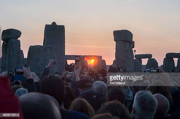 People gather to watch the Summer Solstice sunrise at Stonehenge on June 21 2014 in Wiltshire England A sunny forecast brought thousands of revellers...
