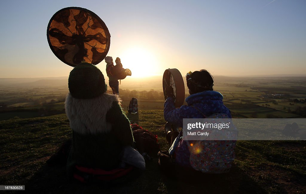 People gather to watch the sun rise as they join in a Beltane dawn celebration service in front of St. Michael's Tower on Glastonbury Tor on May 1, 2013 in Glastonbury, England. Although more synonymous with International Workers' Day, or Labour Day, May Day or Beltane is celebrated by druids and pagans as the beginning of summer and the chance to celebrate the coming of the season of warmth and light. Other traditional English May Day rites and celebrations include Morris dancing and the crowning of a May Queen with celebrations involving a Maypole.