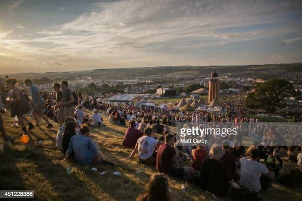 People gather to watch the sun set at Worthy Farm in Pilton on the first day of the 2014 Glastonbury Festival on June 25 2014 in Glastonbury England...