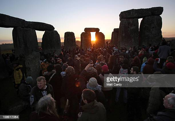People gather to watch the sunrise as druids pagans and revellers celebrate the winter solstice at Stonehenge on December 21 2012 in Wiltshire...