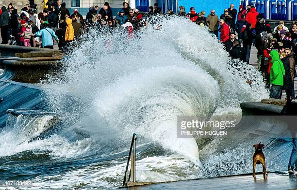 People gather to watch waves breaking on the dyke on March 21 2015 in Wimereux northern France The high tide due on Saturday evening is expected to...