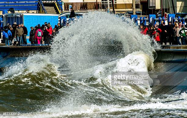 People gather to watch waves breaking on the dyke on March 21 2015 in Wimereux northern France as France's northern coast braces for 'the tide of the...