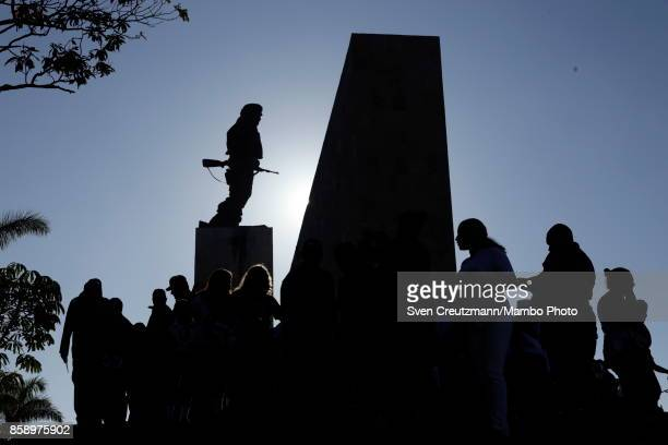 People gather under the statue of Che Guevara after the end of a political act at the Plaza de la Revolucion to celebrate the 50th anniversary of the...