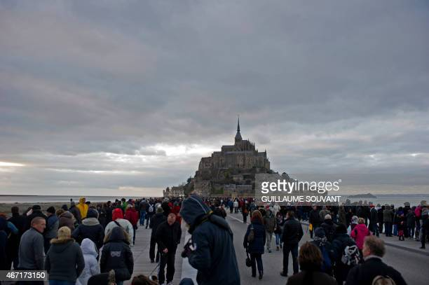 People gather waiting for the wave named 'Mascaret' on the walkway leading to MontSaintMichel on March 21 2015 Thousands of people flocked to Mont...