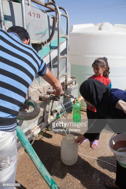 A'ZAZ ALEPPO SYRIA People gather water from a truck at the Syrian refugee camp at the border with Turkey in A'zaz Syria
