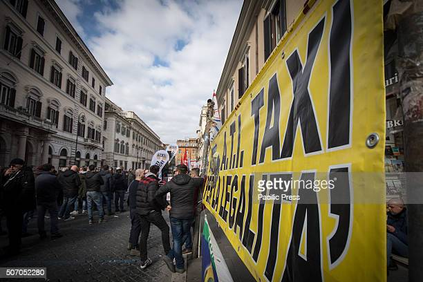 People gather with a big banner during demonstration in Italy Taxi drivers protest in downtown Rome Piazza Santi Apostoli coinciding with the...