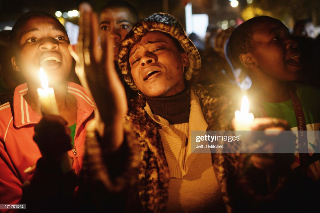 People gather with candles for Nelson Mandela outside the Mediclinic Heart Hospital where he is being treated on June 28, 2013 in Pretoria, South Africa. People continue to gather and lay flowers and tributes outside the Mediclinic Heart Hospital where Mandela is being treated for a lung infection on his 21st day in hospital.