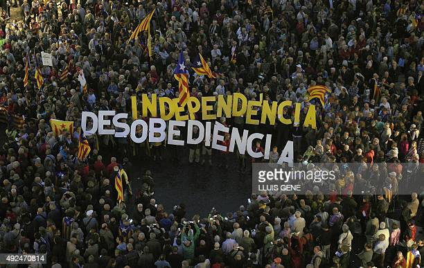 People gather with two banners that read ' Independece' and 'disobedience' during a protest outside Barcelona's City Council on October 13 2015 in...